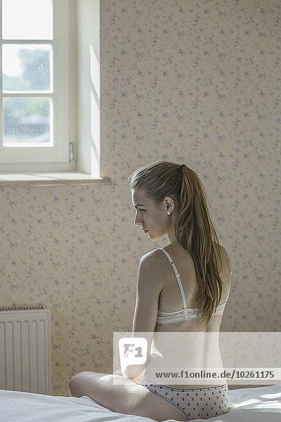 Rückansicht der jungen Frau in Dessous auf dem Bett sitzend