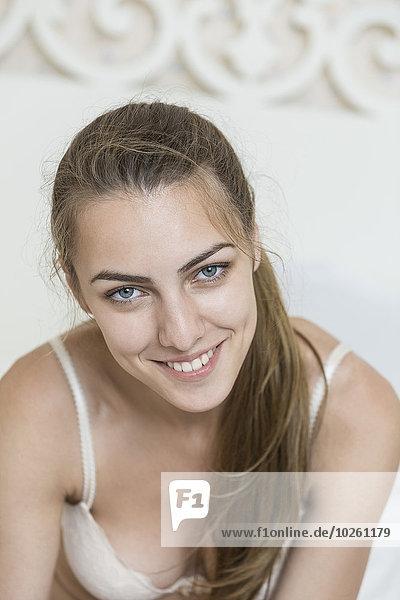 Porträt einer lächelnden jungen Frau mit BH zu Hause