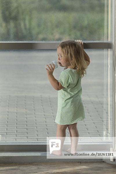 Rückansicht des Mädchens  das Wasser trinkt  während es am Fenster steht