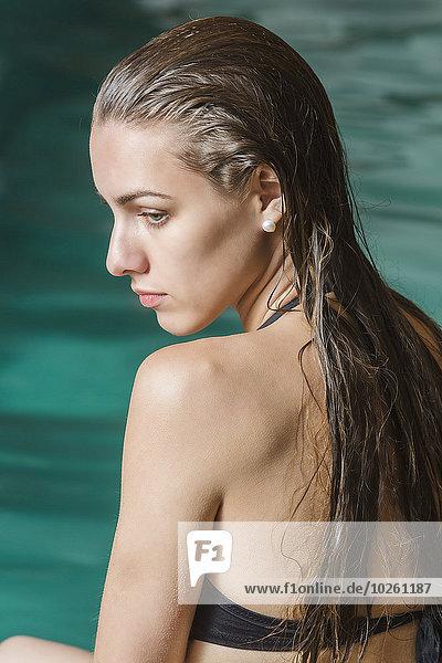 Schöne junge Frau am Pool sitzend