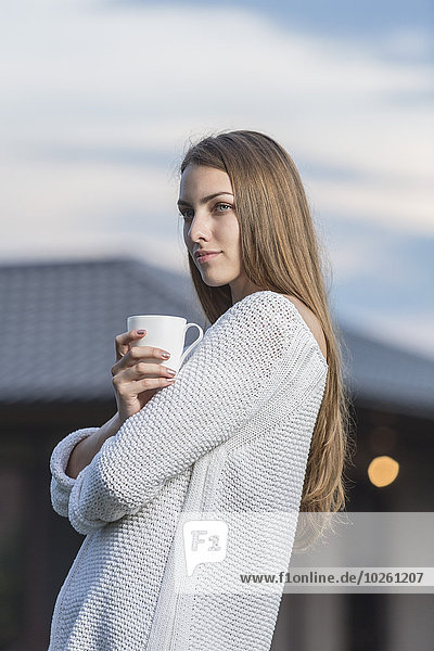 Schöne junge Frau mit Kaffeetasse im Freien