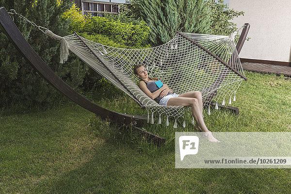 Junge Frau schläft in der Hängematte im Freien