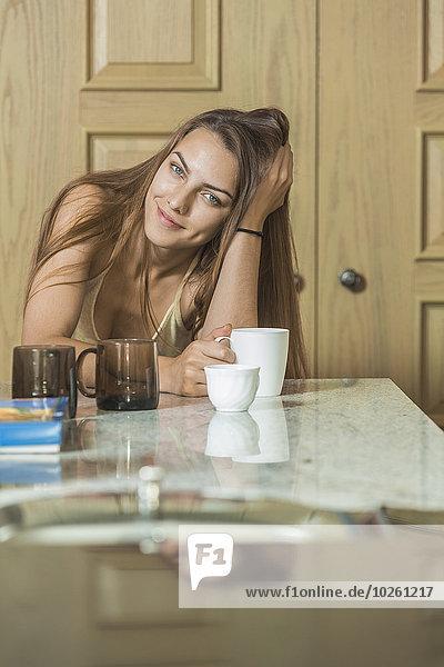 Porträt einer schönen jungen Frau beim Kaffeetrinken am Tisch