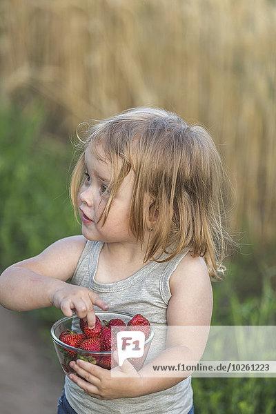 Süßes Mädchen hält eine Schale voller Erdbeeren im Freien.
