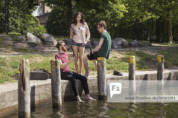 Fröhliche Freunde beim Biergenuss am Kanal im Park
