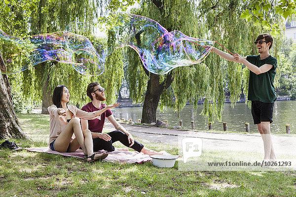 Glückliche Freunde genießen mit großer Blase im Park
