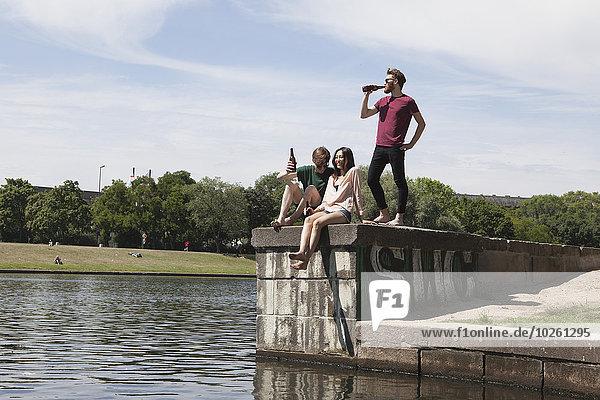 Multi-ethnische Freunde genießen auf der Stützmauer am Kanal