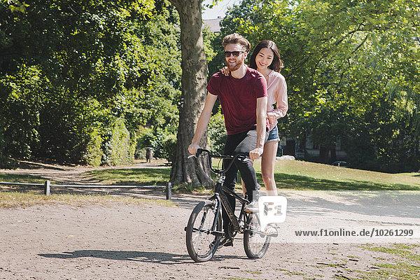 Volle Länge des jungen Paares beim Fahrradfahren im Park