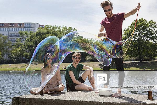 Glückliche Freunde genießen mit großer Blase an der Stützmauer am Kanal im Park