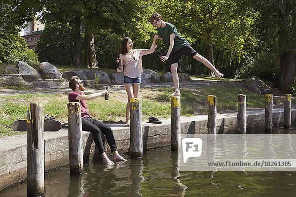 Glückliche Freunde genießen am Kanal im Park