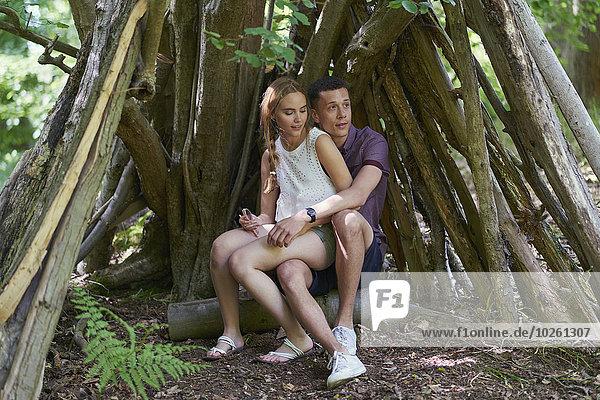 Junge Frau sitzt auf dem Schoß des Mannes unter den Baumstämmen im Park.