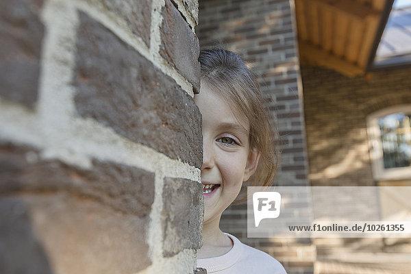 Porträt eines lächelnden Mädchens  das sich hinter einer Ziegelmauer versteckt.