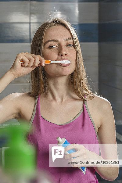 Portrait einer jungen Frau beim Zähneputzen