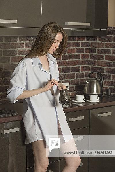 Sinnliche junge Frau im Hemd rührend in der Küche