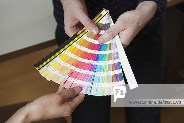 Mittelteil der Geschäftskollegen mit Farbmustern im Büro
