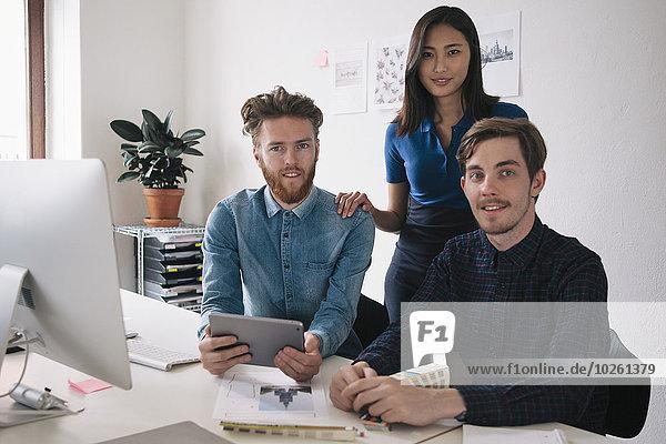 Porträt von selbstbewussten Geschäftsleuten am Schreibtisch im Büro