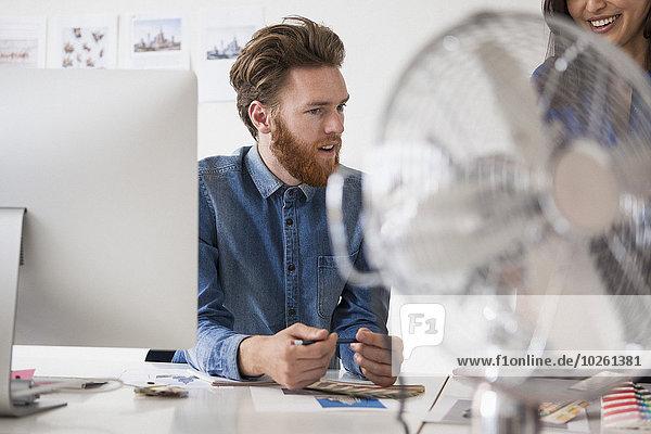 Jungunternehmerin kommuniziert mit Kollegin am Schreibtisch