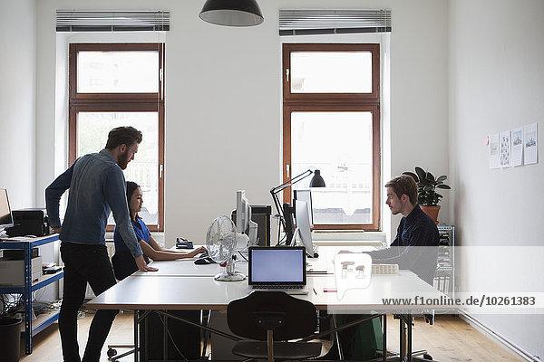 Geschäftsleute,  die am Computertisch im Büro arbeiten