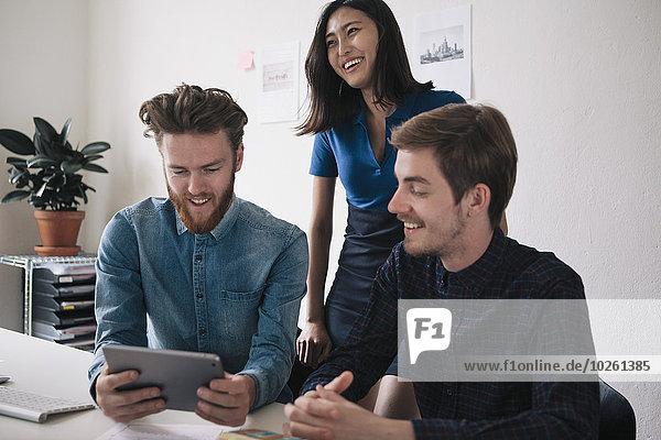 Glückliche Geschäftsleute mit digitalem Tablett im Büro