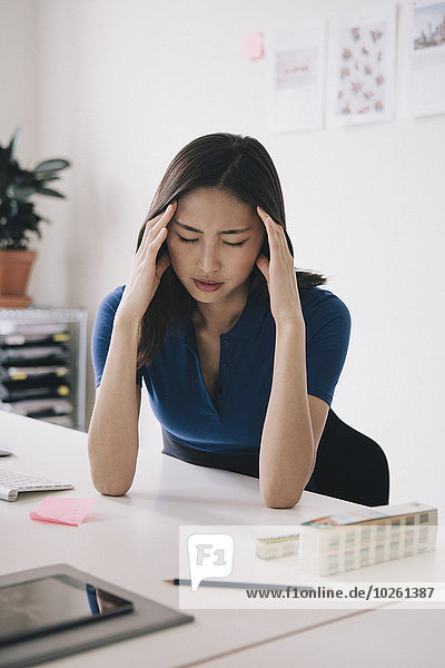 Junge Geschäftsfrau mit Kopfschmerzen am Schreibtisch