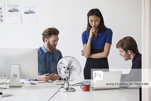 Junge Geschäftsleute diskutieren am Schreibtisch