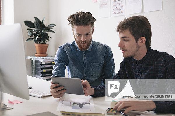 Junge Geschäftsleute  die gemeinsam am Schreibtisch ein digitales Tablett benutzen