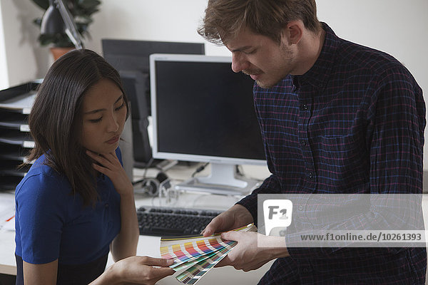 Junge Geschäftskolleginnen und Geschäftskollegen wählen Farbe aus Mustern im Büro