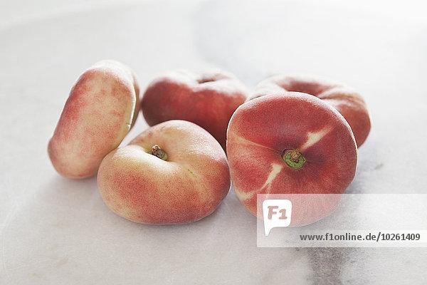 Nahaufnahme von Pfirsichen auf weißem Grund