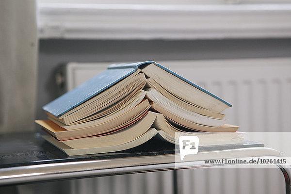 Nahaufnahme von gestapelten offenen Büchern auf dem Tisch