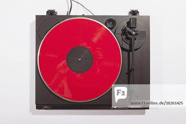 Rote Schallplatte auf Plattenspieler auf weißem Hintergrund