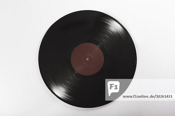 Nahaufnahme einer schwarzen Schallplatte auf weißem Hintergrund