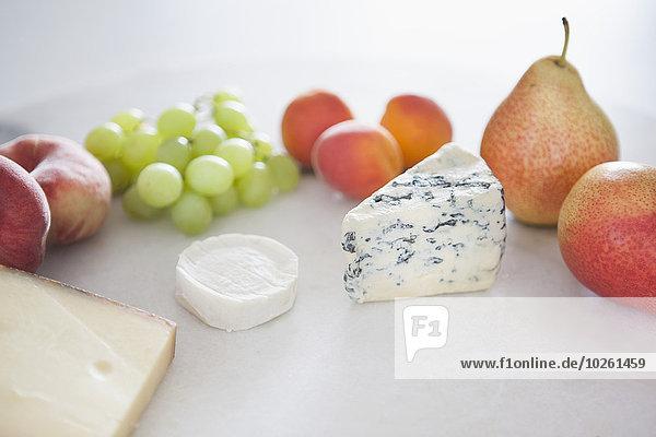 Früchte und Käse im Teller vor weißem Hintergrund