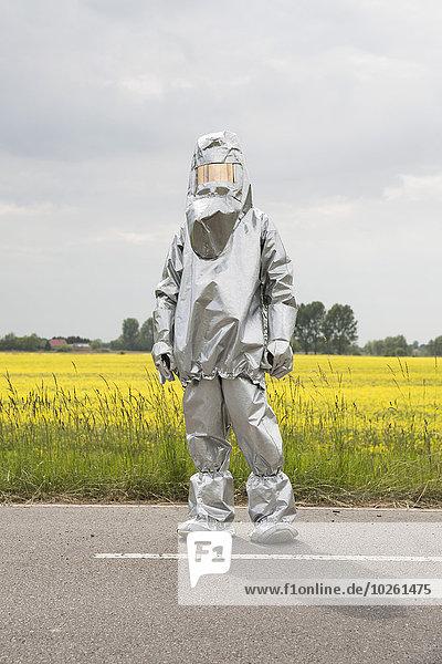 Eine Person im Strahlenschutzanzug steht vor einem Rapsfeld