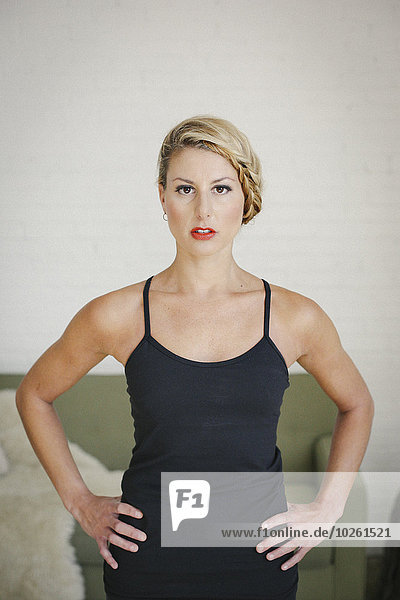 A blonde woman in a black leotard with her hands on her hips  looking at the camera.