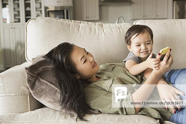 Handy liegend liegen liegt liegendes liegender liegende daliegen Frau sehen Couch lächeln Sohn jung umarmen