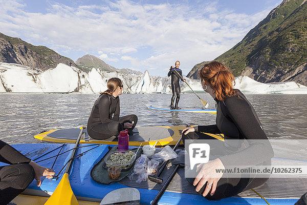 hoch oben sitzend Frau Mittagspause Pause frontal Paddel aufblasen Holzbrett Brett 3 essen essend isst Kachemak Alaska Bucht Grewingk Glacier