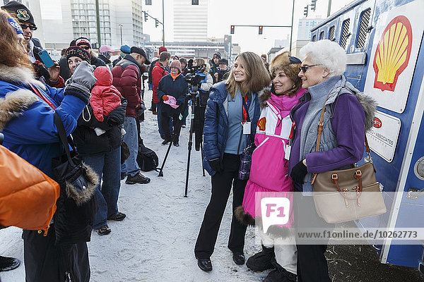 Fans gather around DeeDee Jonrowe prior to the Iditarod 2014 Ceremonial start in downtown Anchorage  Alaska. Iditarod Sled Dog Race 2014 PHOTO (c) BY JEFF SCHULTZ/IditarodPhotos.com -- REPRODUCTION PROHIBITED WITHOUT PERMISSION