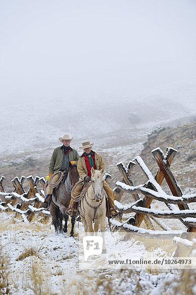 Vereinigte Staaten von Amerika USA nebeneinander neben Seite an Seite Zaun Rocky Mountains Cowgirl Schnee