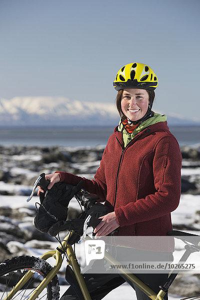 stehend junge Frau junge Frauen folgen Küste Eis vorwärts Fahrrad Rad Stück gefroren