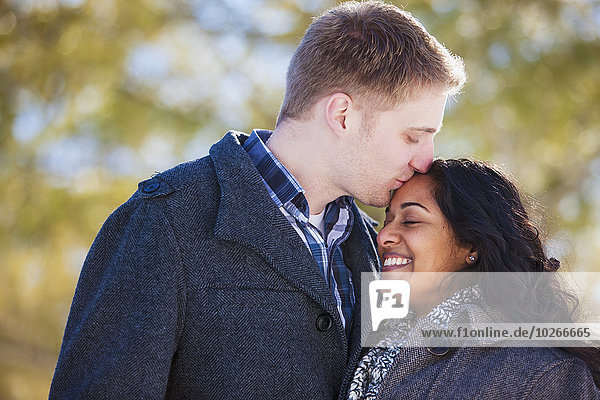 Man in his 20Æs kissing his fiance on the forehead in Scanlon Creek Conservation Area; Ontario,  Canada
