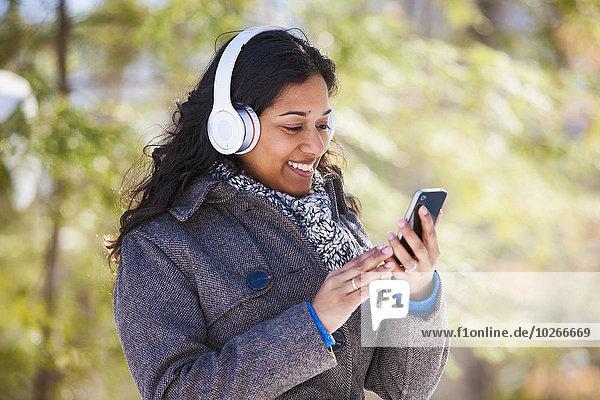 Handy junge Frau junge Frauen benutzen Ethnisches Erscheinungsbild Kopfhörer Schutz Bach Zimmer bluetooth