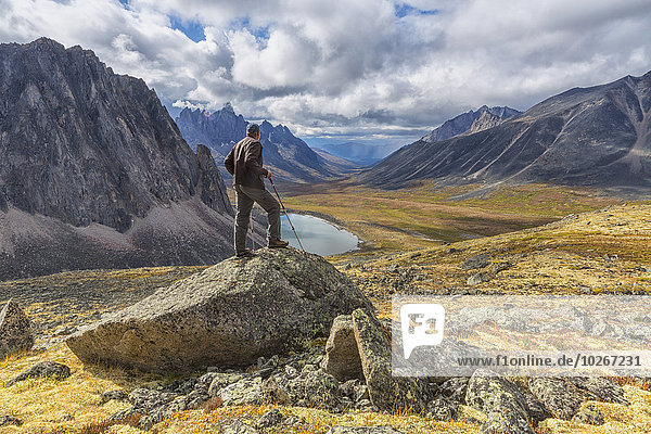 Man standing on a rock overlooking the granite peaks of Tombstone Territorial Park in autumn; Yukon  Canada