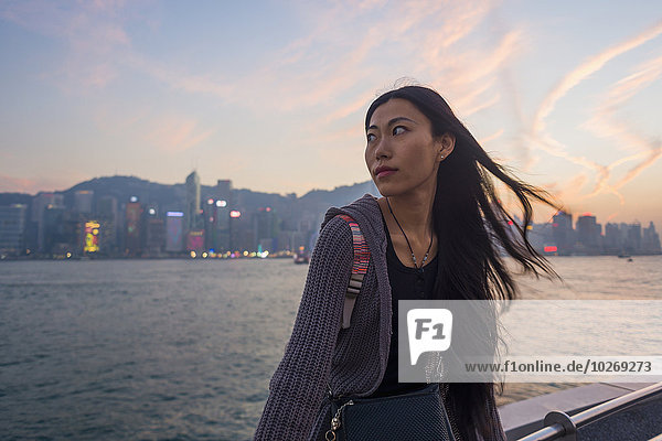 sitzend Skyline Skylines junge Frau junge Frauen Sonnenuntergang Ufer Hintergrund Geländer