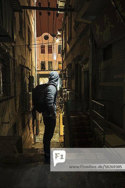 A male traveler looking down a narrow street; Xiamen  Fujian  China