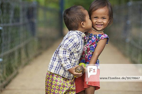 Young boy kissing a young girl; Battambang  Cambodia