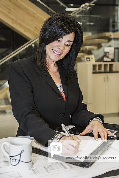 'Professional businesswoman making notes on office interior construction project; Edmonton  Alberta  Canada'