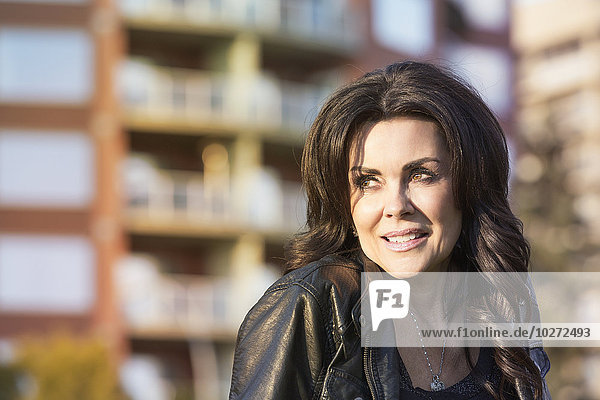 'Portrait of a mature woman outdoors in an urban setting; Edmonton  Alberta  Canada'