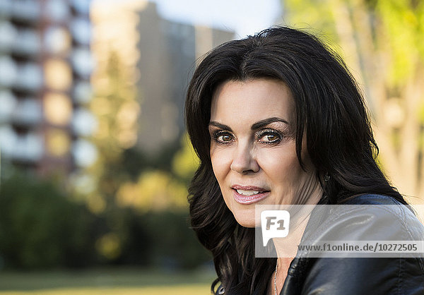 'Portrait of a mature woman outdoors in an urban setting in autumn; Edmonton  Alberta  Canada'