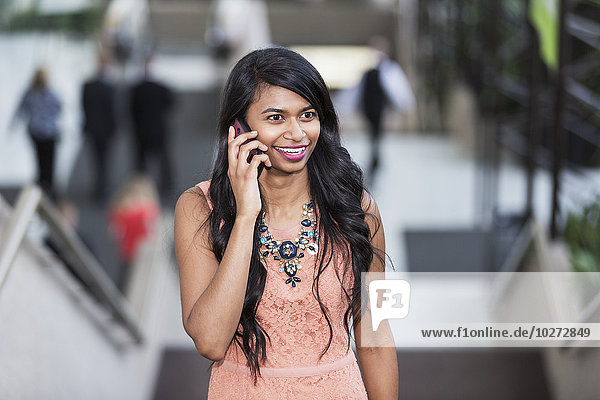 'Young professional businesswoman talking on her smart phone on escalator of office building; Edmonton  Alberta  Canada'