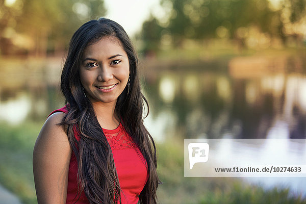 'Portrait of a young Filipino woman in a city park in autumn; St. Albert  Alberta  Canada'